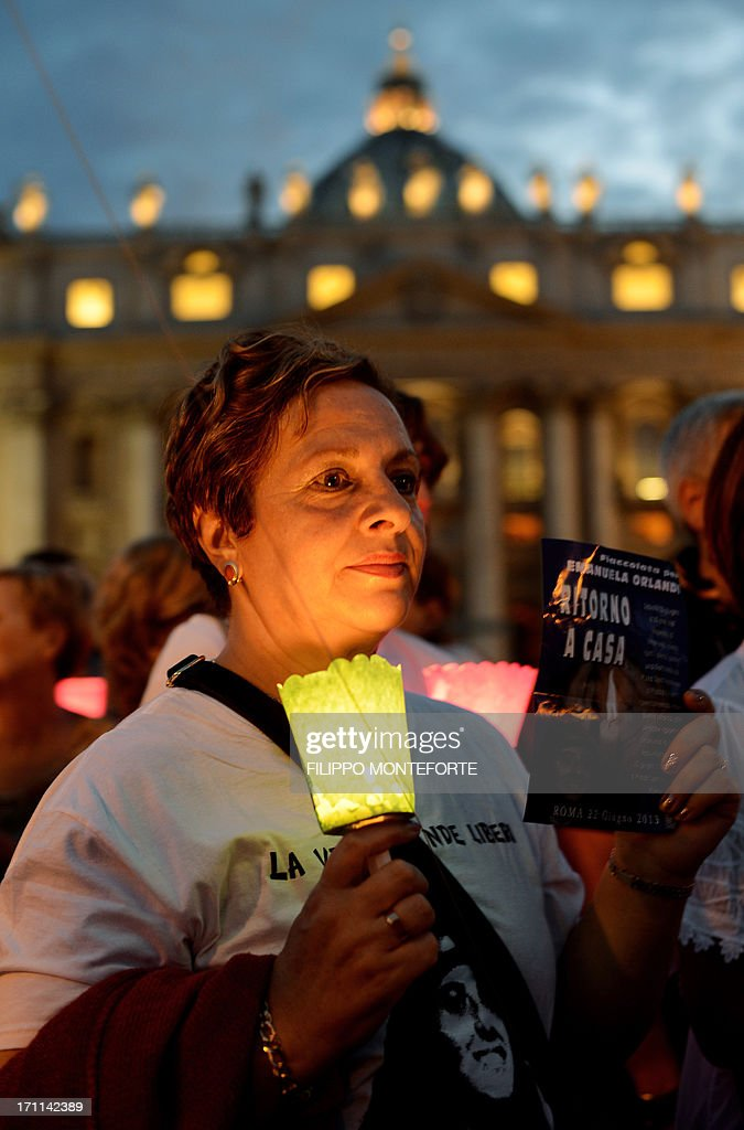 A demonstrator holds a candle during a commemoration of the 30th anniversary of Emanuela Orlandi disappearance in St Peter's Square at the Vatican on June 22 2013. Fifteen-year-old Emanuela Orlandi, the daughter of a Vatican messenger who lived with his family in Vatican City, disappeared on June 22, 1983 when she went to a music lesson. The still unsolved Orlandi saw over the years a number of theories regarding the motives for the crime from claimes that the kidnapping was done by extremist Muslim terrorists to demand the release of Mehmet Ali Agca from prison after he shot pope John Paul II to latest exorcist Gabriele Amorth claiming that she was kidnapped by a member of the Vatican police for sex parties, and then murdered. AFP PHOTO/ Filippo MONTEFORTE