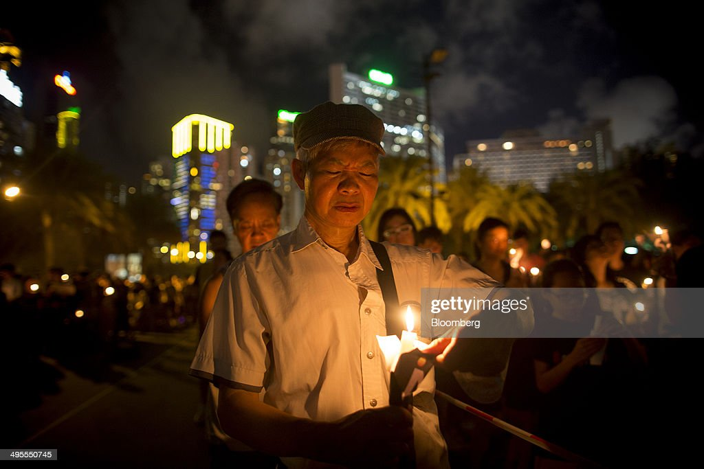 A demonstrator holds a candle during a vigil at Victoria Park in Hong Kong China on Wednesday June 4 2014 Thousands of people attended a vigil in...