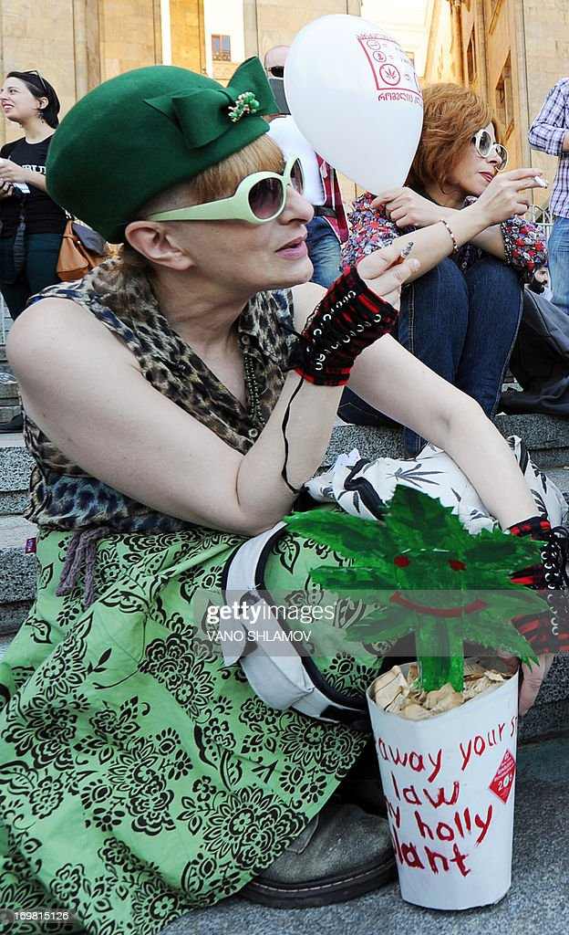 A demonstrator holds a cannabis leaf cut-out as she takes part in a rally for cannabis decriminalization in front of the former parliament building in Tbilisi on June 2, 2013.