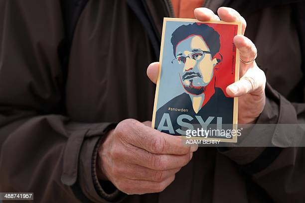 A demonstrator holds a card depicting fugitive US intelligence leaker Edward Snowden during a demonstration in favor of an appearance by Snowden as a...