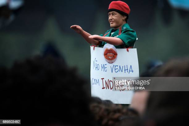 TOPSHOT A demonstrator holds a doll representing former Venezuelan President Hugo Chavez and a sign referring to the demand for direct presidential...