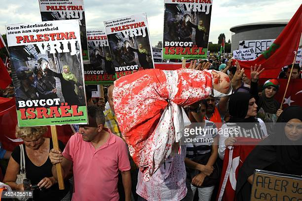 A demonstrator holds a fake child wrapped in a bloody sheet referring to Palestinian children killed during Israel's raids qs others hold posters...