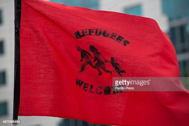 A demonstrator holds a flag declaring 'Refugees Welcome' A collection of activists featuring members on MENA Solidarity Network staged a rally in...