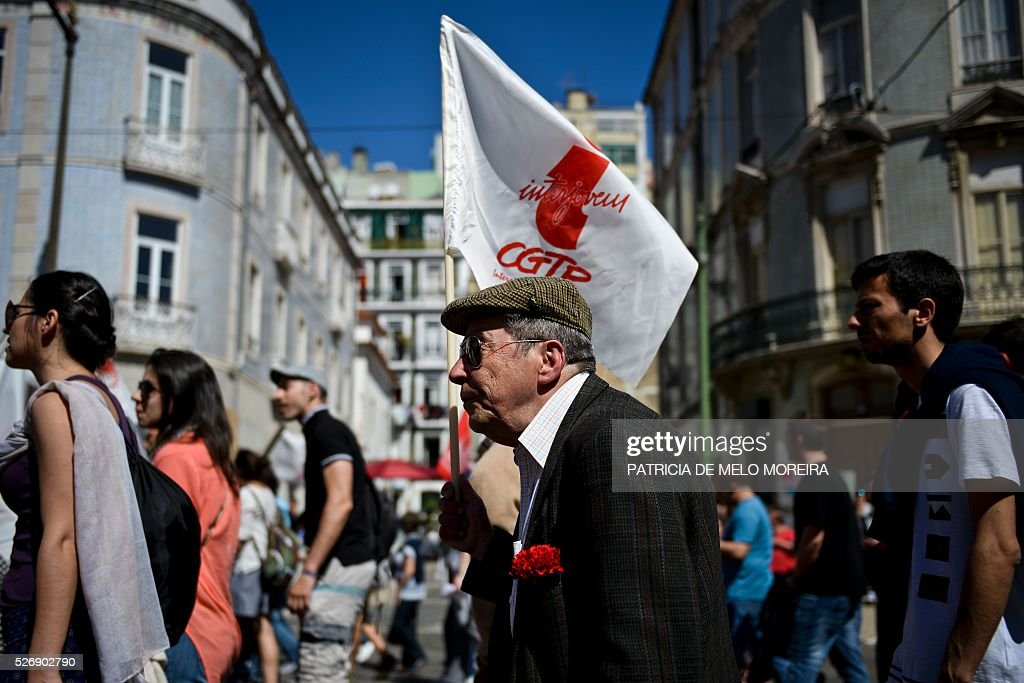 A demonstrator holds a flag during the traditional May Day rally in Lisbon on May 1, 2016. Thousands of people demonstrated today in Lisbon and Portugal's main cities against the government's austerity measures. / AFP / PATRICIA
