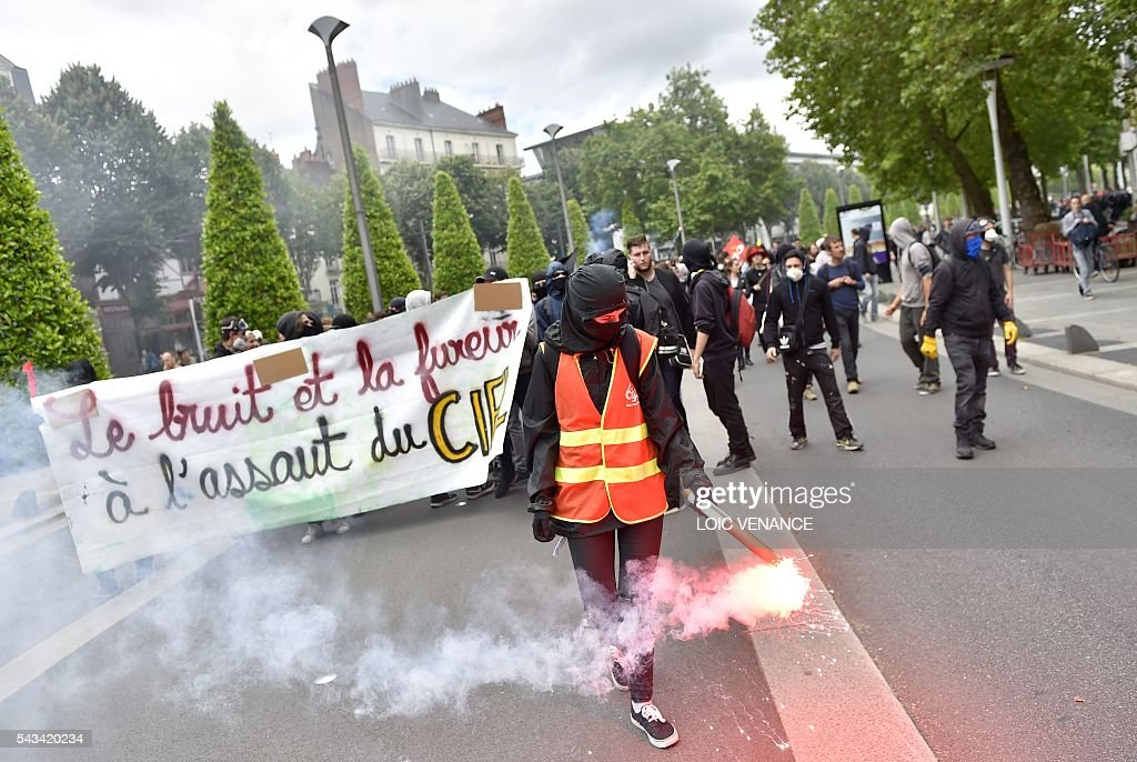 A demonstrator holds a flare during a protest against controversial labour reforms, on June 28, 2016 in Nantes, western France. People took to the streets in France on June 28 in the latest protest march in a marathon campaign against the French Socialist government's job market reforms. Last month the government used a constitutional manoeuvre to push the bill through the lower house without a vote in the face of opposition from Socialist backbenchers. / AFP / LOIC