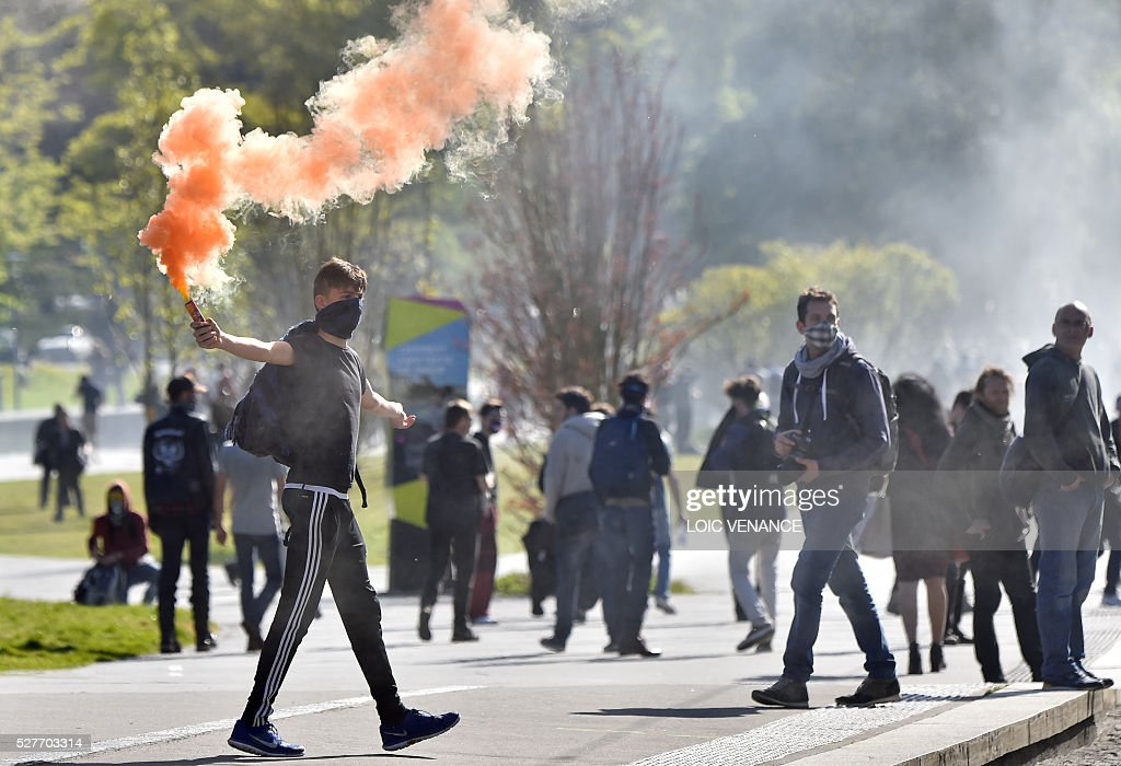 A demonstrator holds a flare during a protest against the government's planned labour law reforms in Nantes, western France, on May 3, 2016. High school pupils and workers protested against deeply unpopular labour reforms that have divided the Socialist government and raised hackles in a country accustomed to iron-clad job security. / AFP / LOIC