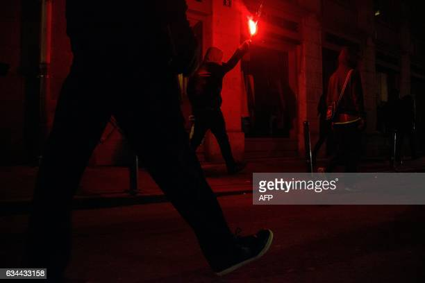 TOPSHOT A demonstrator holds a flare during a protest in support of a man allegedly abused while in police custody in AulnaysousBois on February 9...