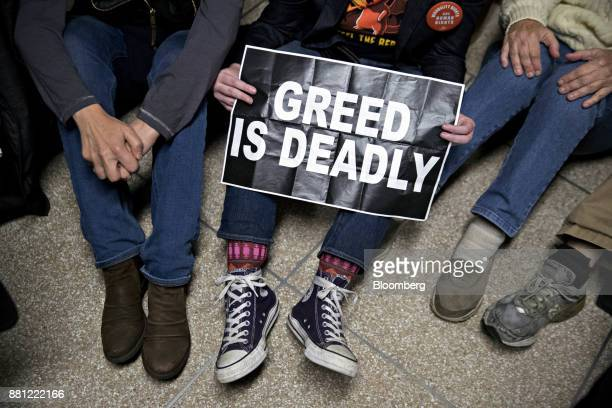 A demonstrator holds a 'Greed Is Deadly' sign after a Senate Budget Committee vote on tax reform in Washington DC US on Tuesday Nov 28 2017 The...