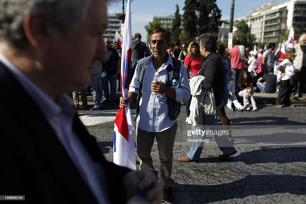 A demonstrator holds a labor union flag during a general strike protest in Athens, Greece, on Tuesday, Nov. 6, 2012. Greece headed for a cliffhanger vote on austerity measures needed to keep the bailout on track as a 48-hour general strike began and European officials squabbled over the timing of a deal to unlock rescue funds. Photographer: Kostas Tsironis/Bloomberg via Getty Images