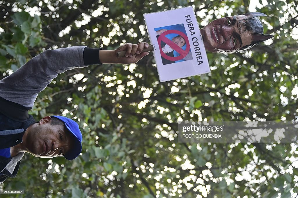 A demonstrator holds a mask depicting Ecuadorean President Rafael Correa as a devil during a protest in Quito on February 10, 2016. AFP PHOTO / RODRIGO BUENDIA / AFP / RODRIGO BUENDIA