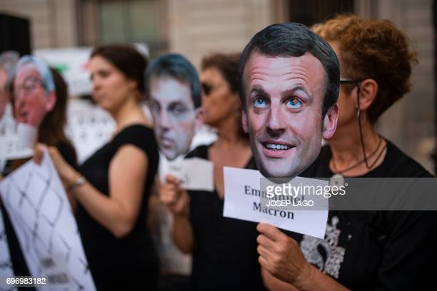 A demonstrator holds a mask with the face of French President Emmanuel Macron during a prorefugees concentration called by more than one hundred...
