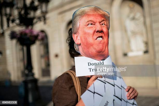 A demonstrator holds a mask with the face of US President Donald Trump during a prorefugees concentration called by more than one hundred...