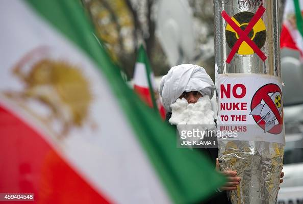 A demonstrator holds a mockup of a nuclear missile with the lettering 'No nuke to the mullahs' as he protests against Iran's nuclear program and...