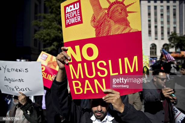 A demonstrator holds a 'No Muslim Ban' sign during a protest in Washington DC US on Wednesday Oct 18 2017 Today a federal judge in Maryland issued a...