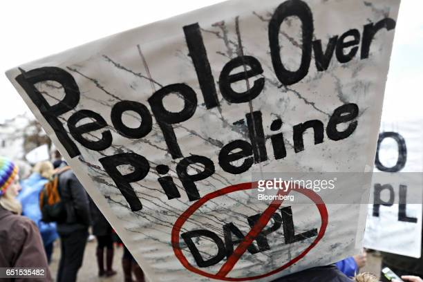A demonstrator holds a 'People Over Pipeline' sign during a protest against the Dakota Access Pipeline in Washington DC US on Friday March 10 2017...