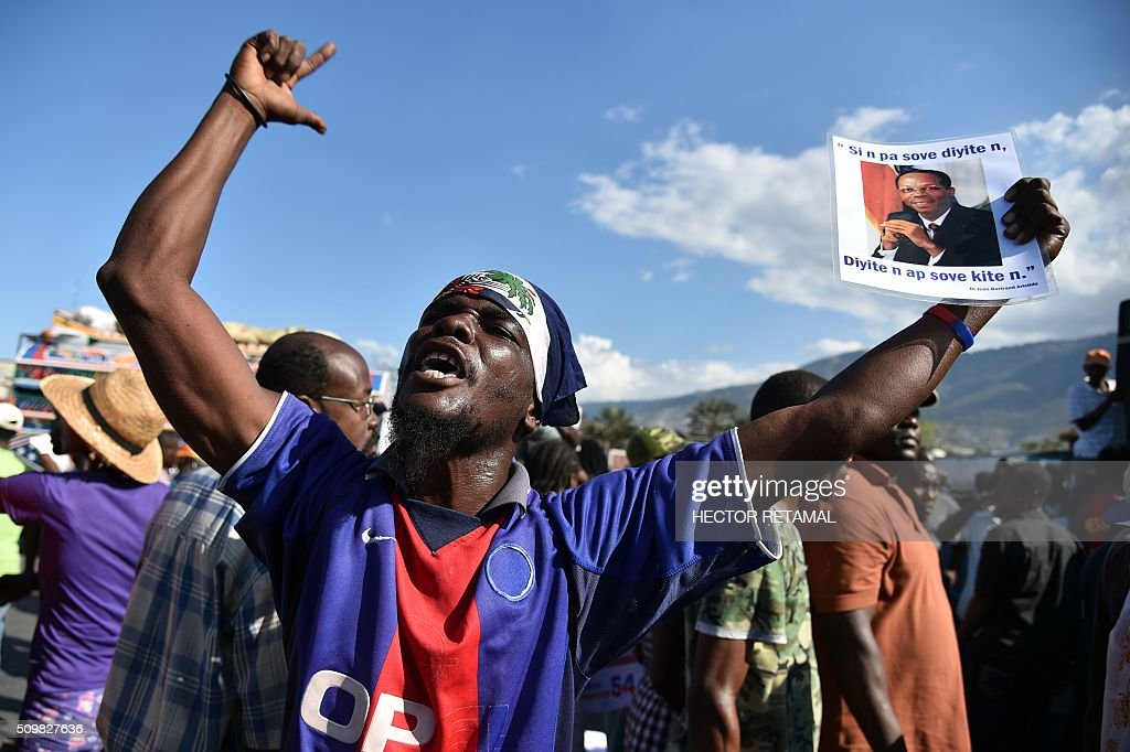 A demonstrator holds a picture of former Haitian President Jean Bertrand Aristide during a march of opposition political parties, in Port-au-Prince, on February 12, 2016, to ask for Jocelerme Privert, current president of the senate to take the provisional presidency of Haiti for a period of two years. Election for a provisonal president will be held on Saturday 13th by the National Assembly and installation is scheduled on Sunday 14th. / AFP / HECTOR RETAMAL
