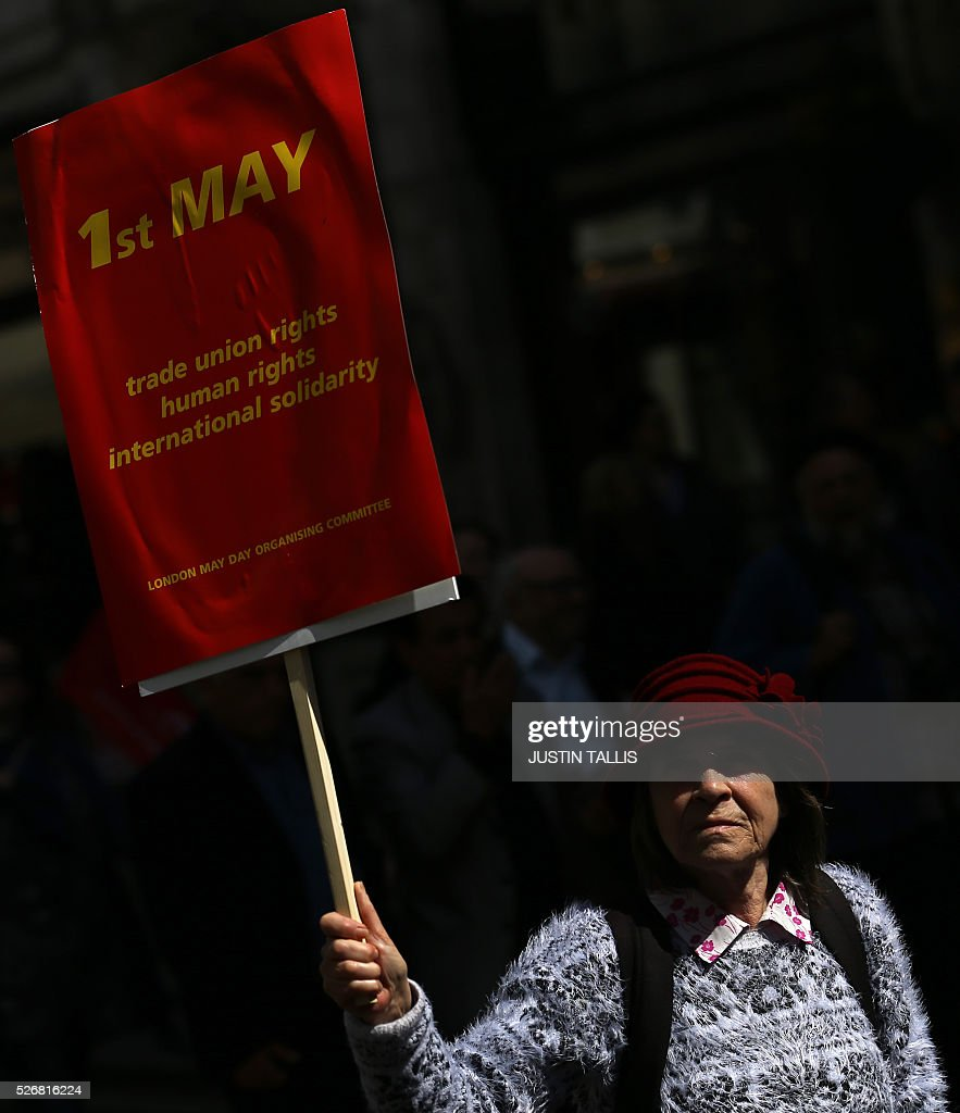 A demonstrator holds a placard as she participates in a May Day rally in London on May 1, 2016. / AFP / JUSTIN