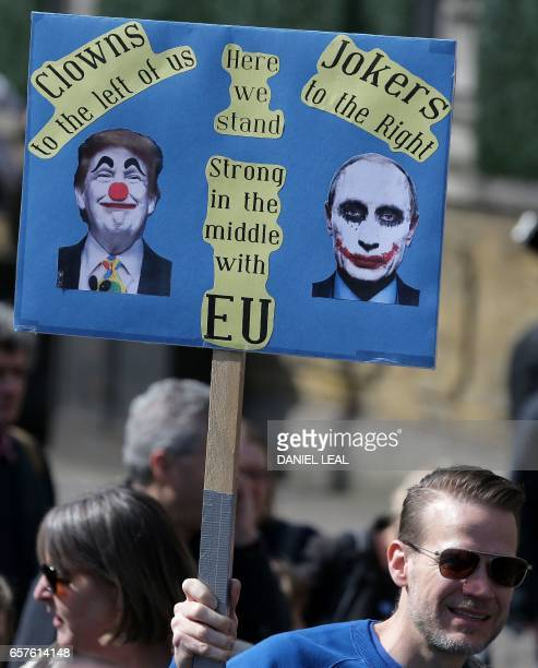 A demonstrator holds a placard depicting US President Donald Trump and Russia's President Vladimir Putin during an anti Brexit proEuropean Union...