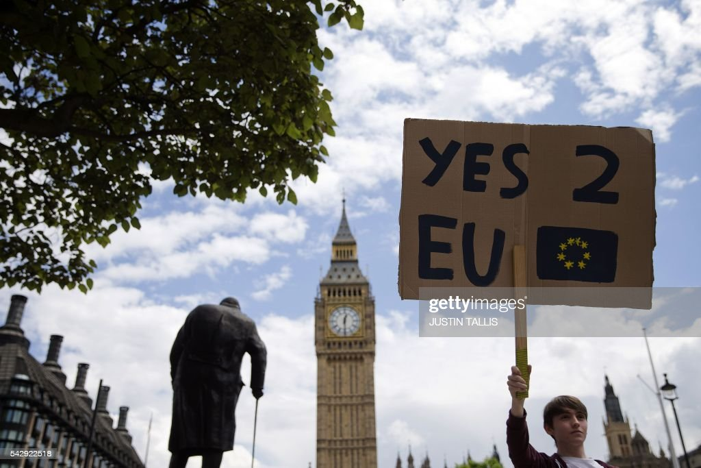 A demonstrator holds a placard during a protest against the outcome of the UK's June 23 referendum on the European Union (EU), in central London on June 25, 2016. The result of Britain's June 23 referendum vote to leave the European Union (EU) has pitted parents against children, cities against rural areas, north against south and university graduates against those with fewer qualifications. London, Scotland and Northern Ireland voted to remain in the EU but Wales and large swathes of England, particularly former industrial hubs in the north with many disaffected workers, backed a Brexit. / AFP / JUSTIN