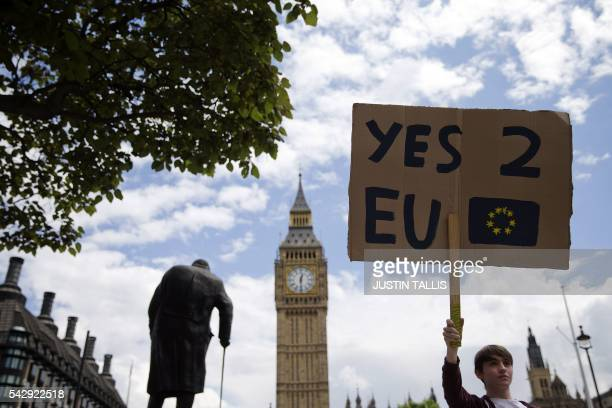 A demonstrator holds a placard during a protest against the outcome of the UK's June 23 referendum on the European Union in central London on June 25...