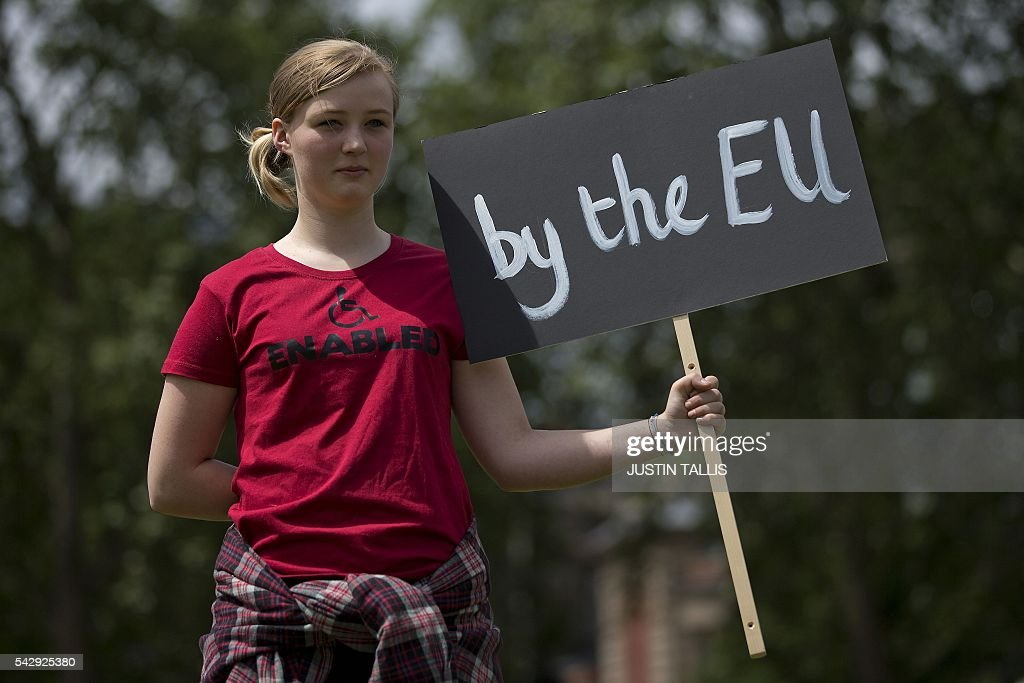 A demonstrator holds a placard during a protest against the pro-Brexit outcome of the UK's June 23 referendum on the European Union (EU), in central London on June 25, 2016. The result of Britain's June 23 referendum vote to leave the European Union (EU) has pitted parents against children, cities against rural areas, north against south and university graduates against those with fewer qualifications. London, Scotland and Northern Ireland voted to remain in the EU but Wales and large swathes of England, particularly former industrial hubs in the north with many disaffected workers, backed a Brexit. / AFP / JUSTIN