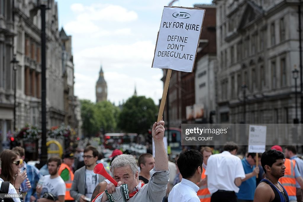 A demonstrator holds a placard during a protest by London black cab drivers against a new private taxi service 'Uber', a mobile phone app, in central London on June 11, 2014. Taxi drivers brought parts of London, Paris and other European cities to a standstill on June 11 as they protested against new private cab apps such as Uber which have shaken up the industry. Thousands of London's iconic black cabs, many of them beeping their horns, filled the roads around Buckingham Palace, Trafalgar Square and the Houses of Parliament to the exclusion of any other vehicles.