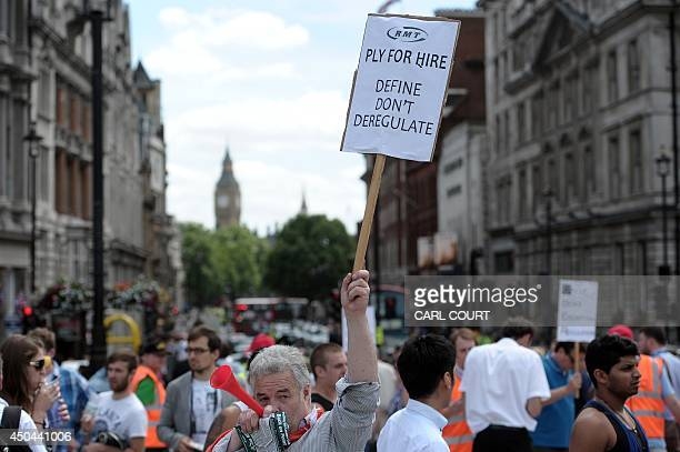 A demonstrator holds a placard during a protest by London Black Cab drivers against a new private taxi service 'Uber' a mobile phone app in central...