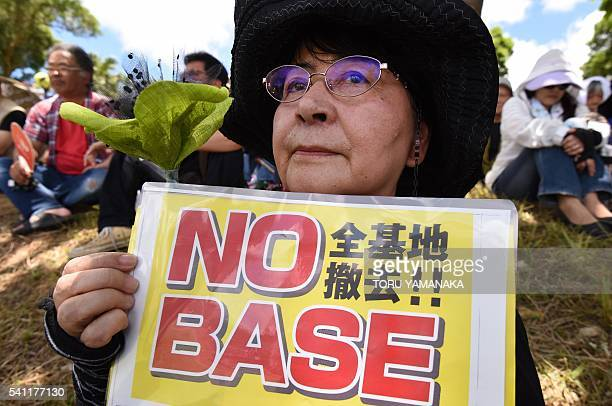 A demonstrator holds a placard during a rally against the US military presence in Naha Okinawa prefecture on June 19 following the alleged rape and...