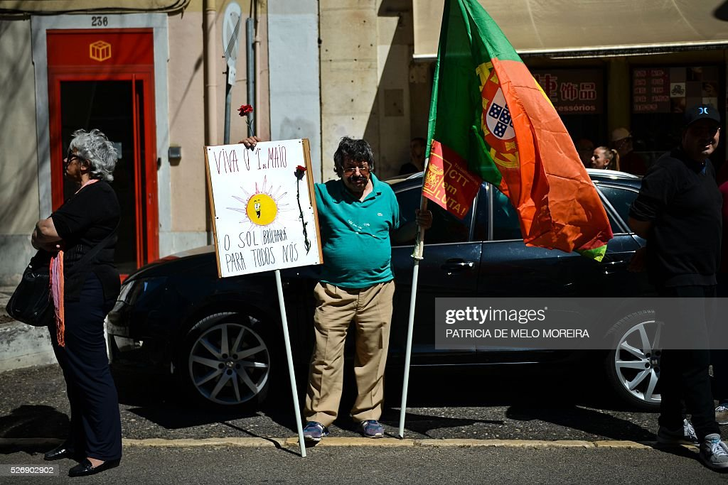 A demonstrator hold a placard reading '1st May, The sun will shine for all of us' and the Portuguese flag during the traditional May Day rally in Lisbon on May 1, 2016. Thousands of people demonstrated today in Lisbon and Portugal's main cities against the government's austerity measures. / AFP / PATRICIA
