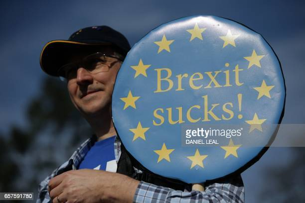 TOPSHOT A demonstrator holds a placard reading 'Brexit Sucks' as he participates in an anti Brexit proEuropean Union march in London on March 25...