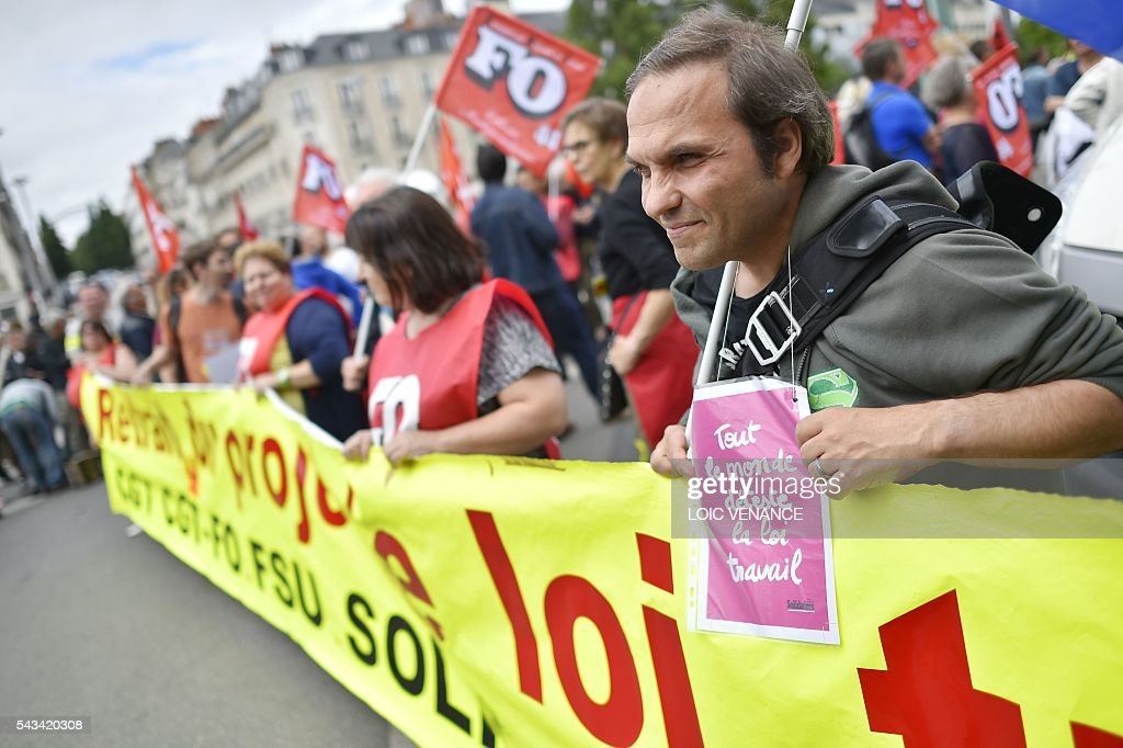A demonstrator holds a placard reading 'everybody hates the labour law' during a protest against controversial labour reforms, on June 28, 2016 in Nantes, western France. People took to the streets in France on June 28 in the latest protest march in a marathon campaign against the French Socialist government's job market reforms. Last month the government used a constitutional manoeuvre to push the bill through the lower house without a vote in the face of opposition from Socialist backbenchers. / AFP / LOIC