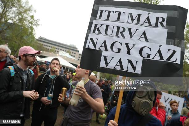 A demonstrator holds a placard reading 'Here is a fucking big gas' during a protest against Hungarian Prime Minister Viktor Orban's government in...