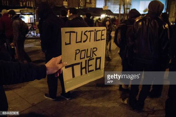 TOPSHOT A demonstrator holds a placard reading 'Justice for Theo' as people take to the street during a protest in support of a man allegedly abused...