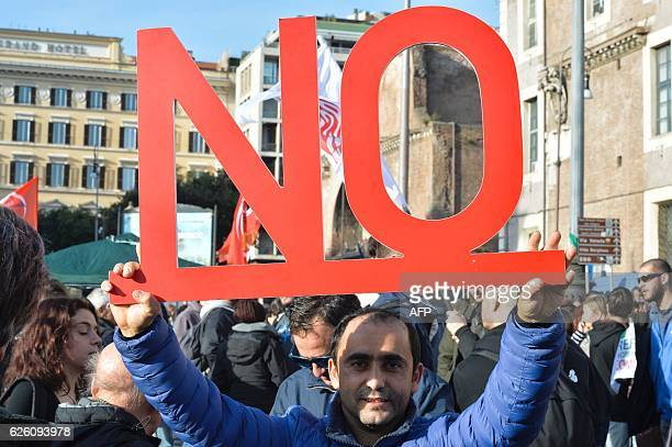 A demonstrator holds a placard reading 'no' during a demonstration of the 'C'e chi dice no' movement calling for a 'no' vote to the upcoming...