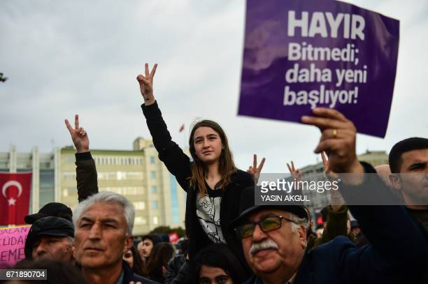 A demonstrator holds a placard reading 'NO This is just the beginning' and others gesture during a protest at the Kadikoy district in Istanbul on...