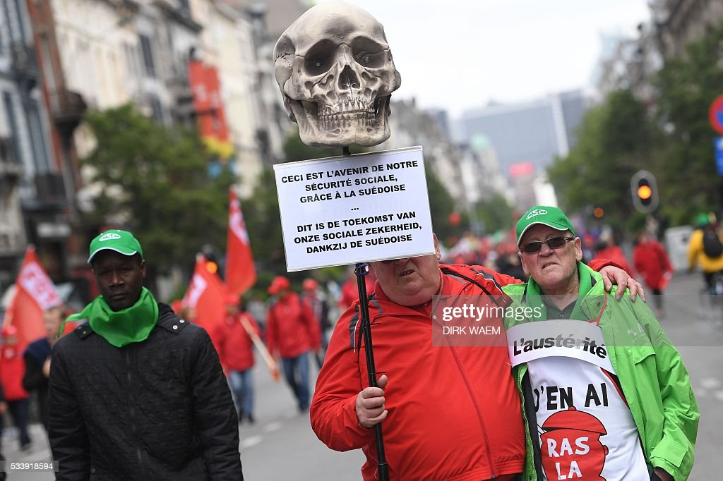 A demonstrator holds a placard reading 'This is the future of our social insurance', during a national anti-austerity protest on May 24, 2016, in Brussels. Belgian trade unions called for mass protests against the centre-right government's proposed work reforms as they plan rallies and strikes over the next few months. / AFP / Belga / DIRK WAEM / Belgium OUT