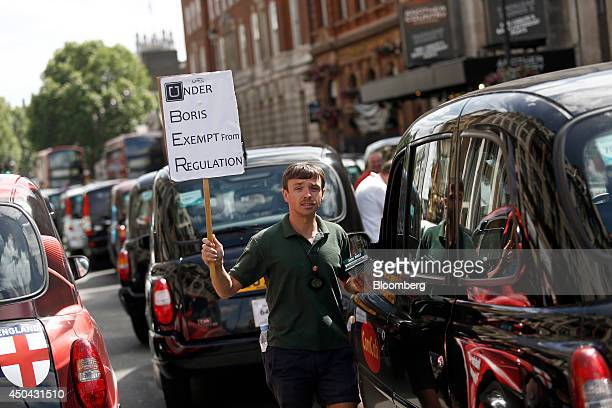 A demonstrator holds a placard reading 'Under Boris Exempt From Regulation ' as he stands beside parked London taxi cabs on Whitehall during a...