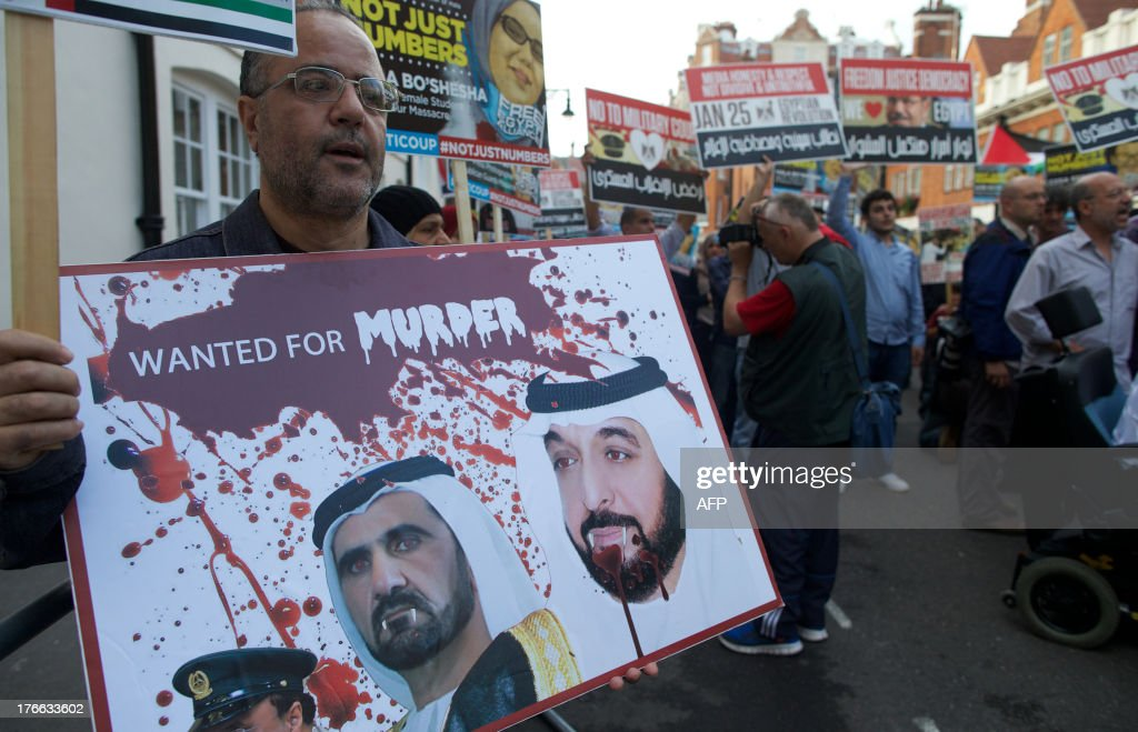 A demonstrator holds a placard showing defaced faces of bearing the face of Dubai ruler Sheikh Mohammed bin Rashid al-Maktoum and Emirati President Sheikh Khalifa bin Zayed al-Nahayan during a protest against the killing of Morsi supporters in Egypt outside the Egyptian embassy in London on August 16, 2013. Scores of demonstrators gathered with placards outside the Egyptian embassy in London to join a 'day of anger' over the violence and killing in Egypt during an ongoing deadly crackdown by security forces on Islamist demonstrators. The United Arab Emirates voiced support for the deadly assault by Egypt's security forces on Islamist supporters of ousted president Mohamed Morsi, saying it was the state's duty to restore order.