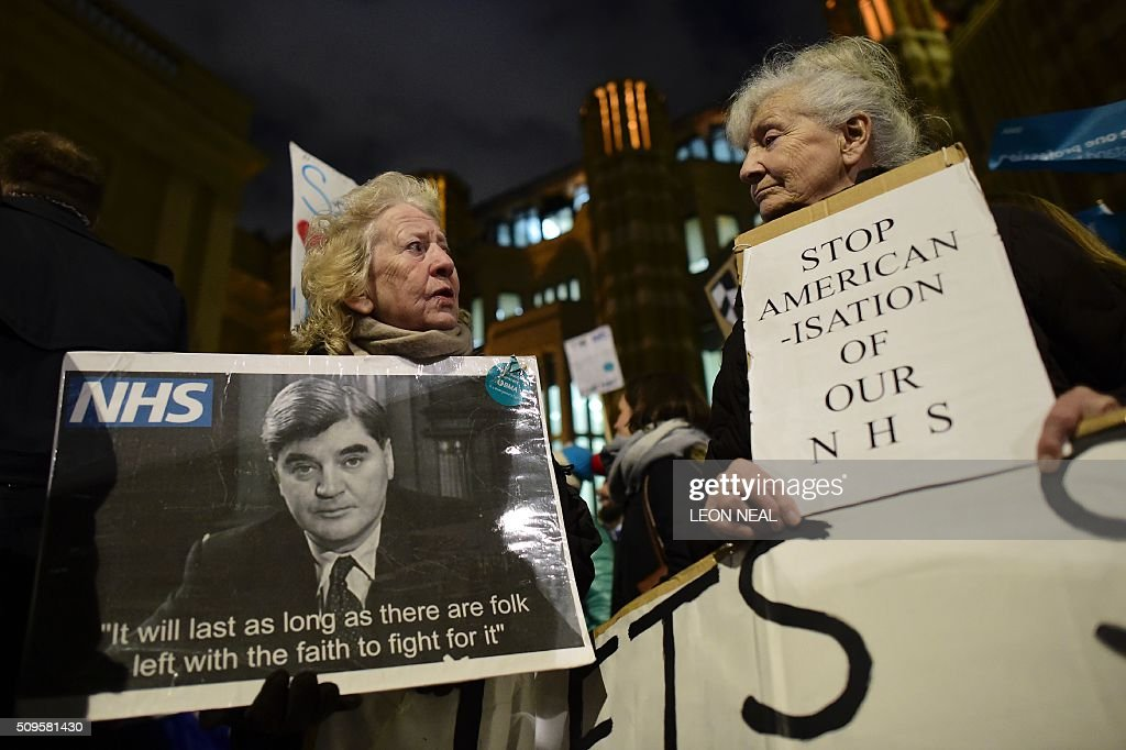 A demonstrator (L) holds a placard showing former Health Secretary Aneurin Bevan, the minister who spearheaded the creation of the National Health Service (NHS), as she joins others including junior doctors with placards outside the Department of Health on Whitehall in central London on February 11, 2016, to protest following the annoucement of the government decision to impose new contracts on junior doctors. Britain's government said February 11 it would impose new contracts on junior doctors to force an end to strikes over changes to their working conditions. Health Secretary Jeremy Hunt told the House of Commons that the decision had been taken after negotiations with doctors' union the British Medical Association (BMA) failed. The announcement came after nearly three years of negotiations and the day after a second 24-hour strike led to nearly 3,000 operations being postponed in England. NEAL