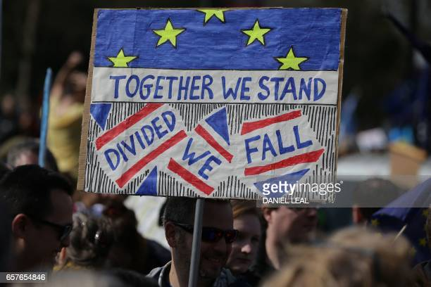 A demonstrator holds a placard that reads ' Together we Stand Dived we Fall' as he prepares to participate in an anti Brexit proEuropean Union march...