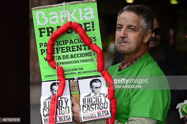 A demonstrator holds a placard wrapped with fakes sausages and depicting Former IMF head Rodrigo Rato as Rato arrives for a hearing in Madrid on...