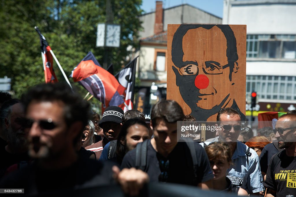 A demonstrator holds a portrait of French socialist President François Hollande. during a protest against the El-Khomri bill on labour reforms the day the bill go through the Senate. They also protest against the use of article 49.3 which bypass the Parliament . Toulouse. France. June 28th, 2016.