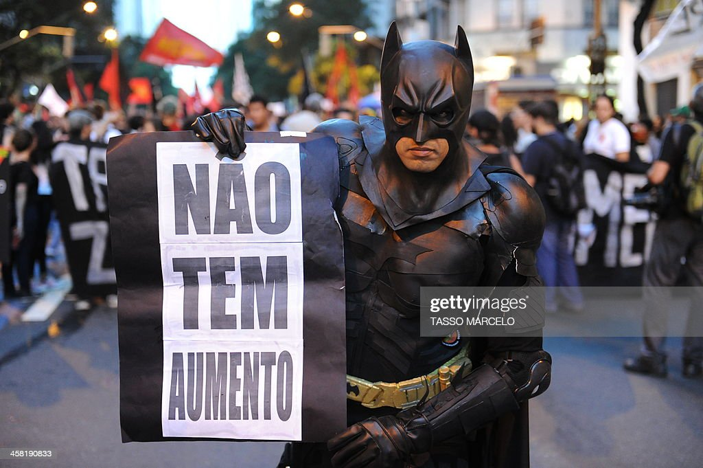 A demonstrator holds a poster against a public transport fare hike announced for January 2014 by Rio de Janeiro's Mayor Eduardo Paes, during a protest in the streets of the Brazilian city, on December 20, 2013.