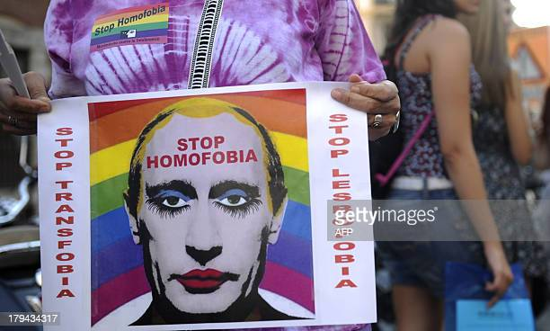 A demonstrator holds a poster depicting Russian President Vladimir Putin with makeup as he protests against homophobia and repression against gays in...