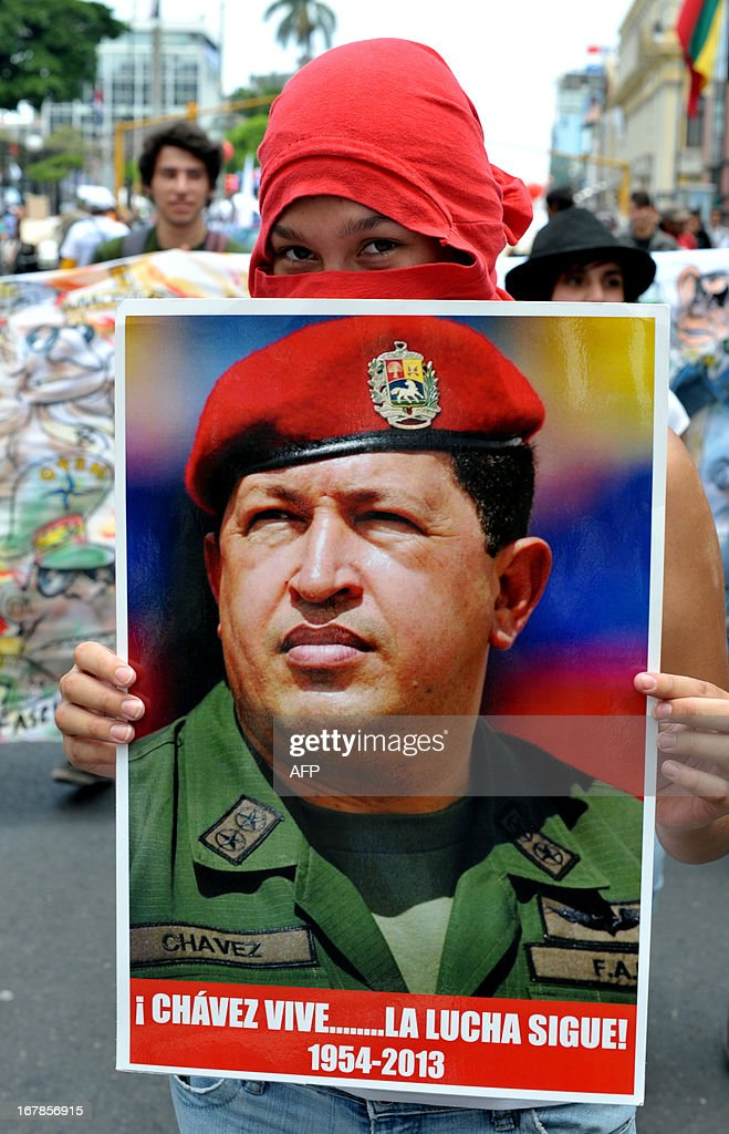 A demonstrator holds a poster of former Venezuelan President Hugo Chavez reading 'Chavez lives...The fight continues!', during a May Day rally in San Jose on May 1, 2013. AFP PHOTO/Ezequiel BECERRA