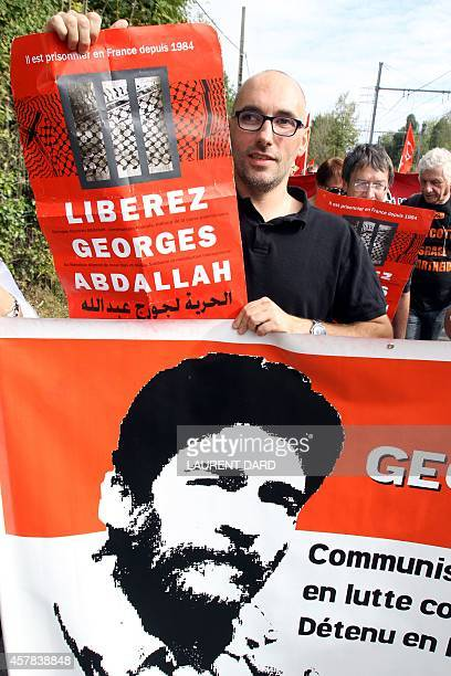 A demonstrator holds a poster reading 'Free Georges Abdallah' as around 300 people gather to call for the release of 'Lebanese revolutionary' Georges...