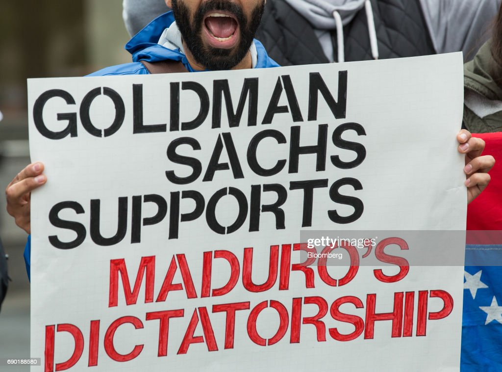 A demonstrator holds a sign and chants during a protest outside of the Goldman Sachs Group Inc. headquarters in New York, U.S., on Tuesday, May 30, 2017. Goldman faces a probe by Venezuela's opposition leaders after buying bonds issued in 2014 by the state oil company, a purchase some lawmakers said bolsters President Nicolas Maduro as he grapples with accusations of human-rights violations. Photographer: Alexander F. Yuan/Bloomberg via Getty Images