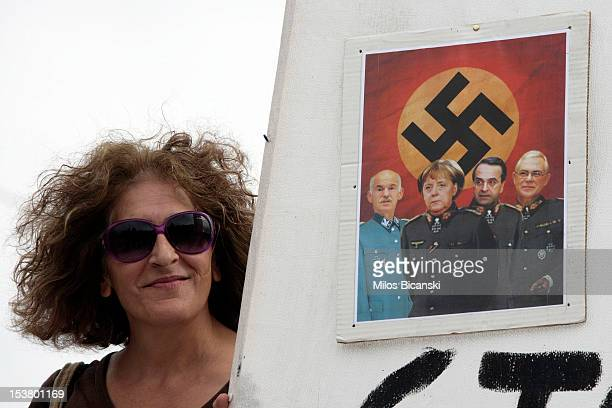 A demonstrator holds a sign depicting German Chancellor Angela Merkel and three recent Greek prime ministers in Nazi uniforms during a protest...