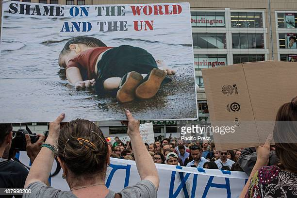 A demonstrator holds a sign displaying the famed image of a Syrian refugee child found dead on the shore A collection of activists featuring members...