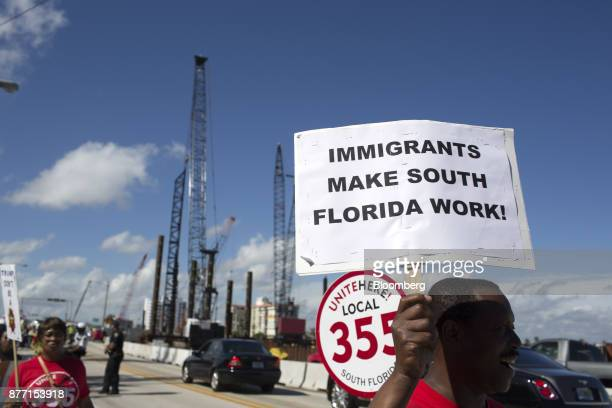 A demonstrator holds a sign during a protest ahead of the arrival of US President Donald Trump at MaraLago in West Palm Beach Florida US on Tuesday...